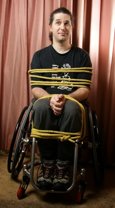Photo of a man tied with thick rope to his wheelchair