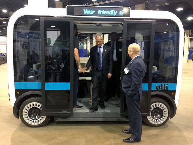 The Olli self-driving bus shown from the side with door opened and a man about to get out of it.