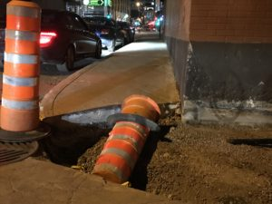 Curb cut on a badly lit corner at night, dug up with construction.