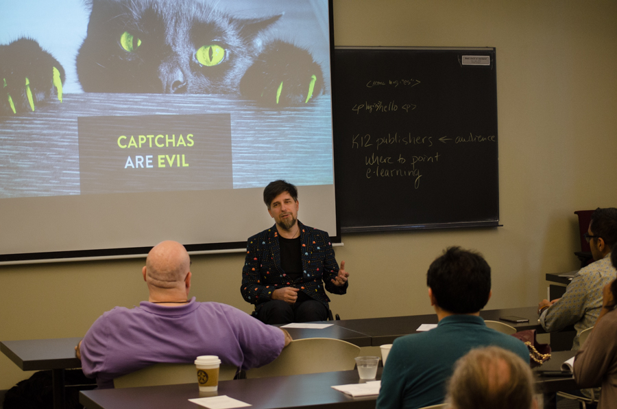 "Nic Steenhout talking to class attendees in front of a slide with a cat. The caption reads ""CAPTCHAs are evil"""